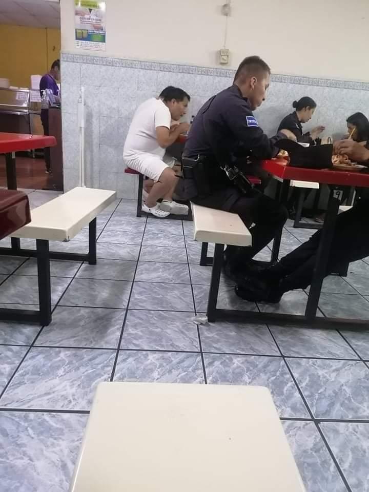 Reos comen en una pupusería del país junto a agentes de la PNC